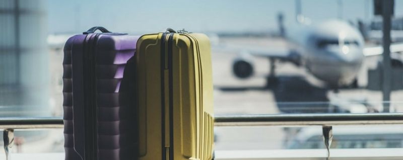 purple and yellow luggage in airport