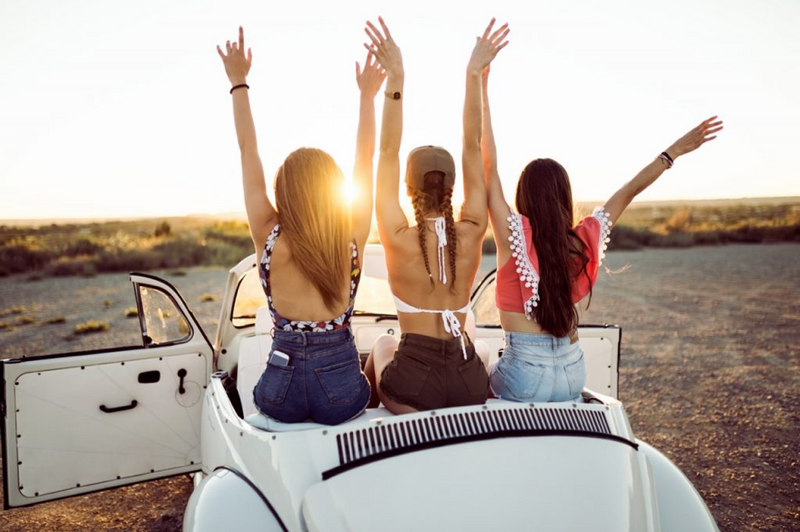 carefree girls on holiday sunset in car
