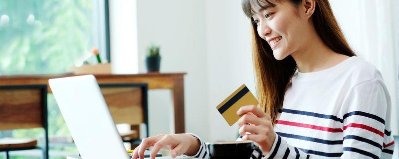 Happy woman using credit card - SingSaver