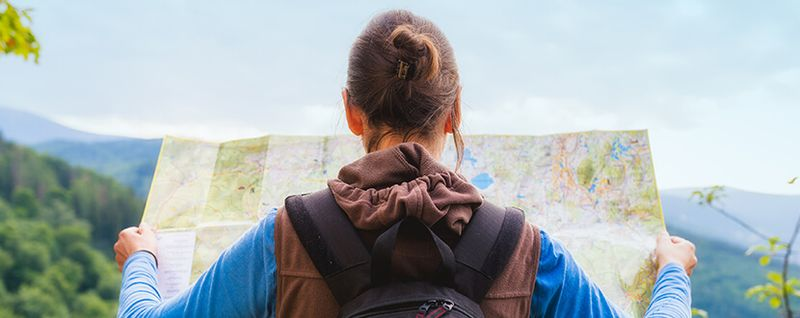 Backpacker looking at the map for directions - SingSaver