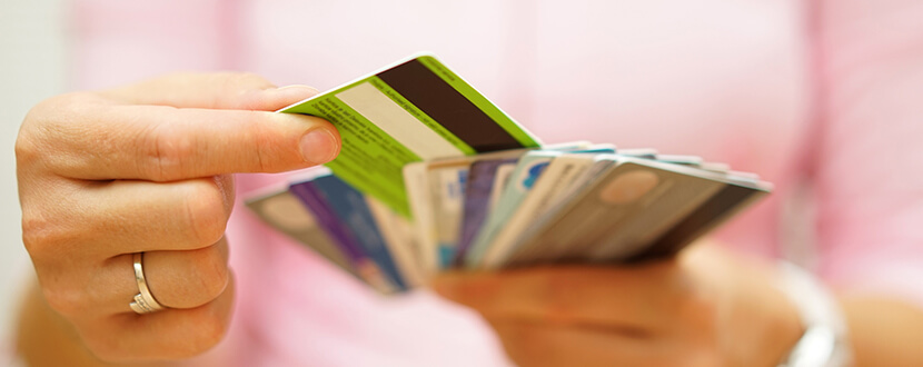 person arranging credit cards in hand -SingSaver