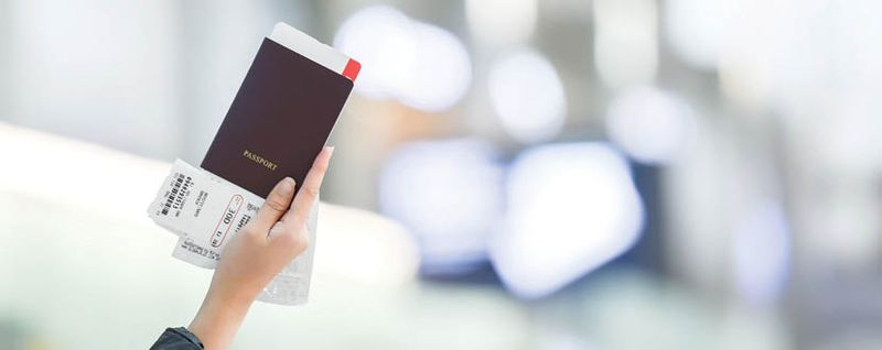person holding passport in airport -SingSaver