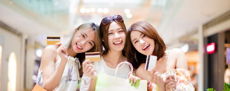 Three friends holding shopping bags and credit cards