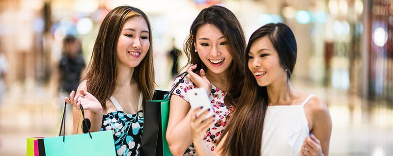 3 ladies in shopping mall looking at mobile phone -SingSaver
