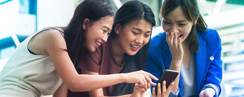 Friends laughing and looking at a phone -SingSaver